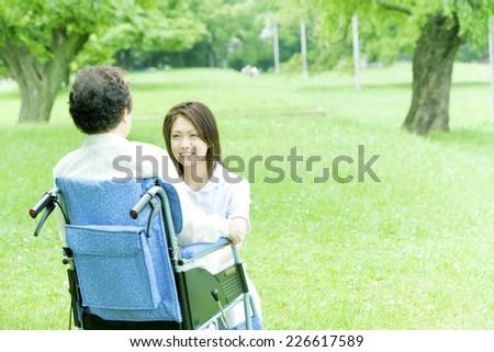 Nurse and senior woman in wheelchair - stock photo