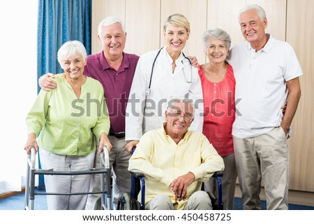 Nurse and seniors standing together in a retirement home - stock photo