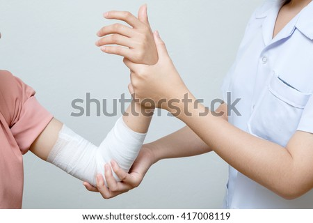 Nurse applying bandage to patient injured elbow - stock photo