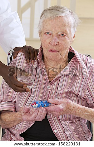 nurse assisting disabled elderly woman to take medicine - stock photo
