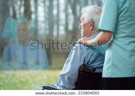 Nurse assisting disabled senior man using wheelchair - stock photo