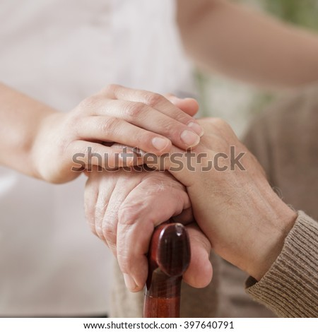 Nurse assisting ill elder man - stock photo