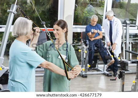 Nurse Assisting Senior Woman With Resistance Band Exercise - stock photo