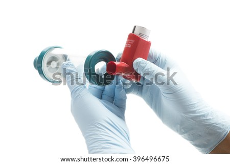 Nurse attaches spacer chamber to asthma inhaler.  Albuterol is a common medication name. - stock photo