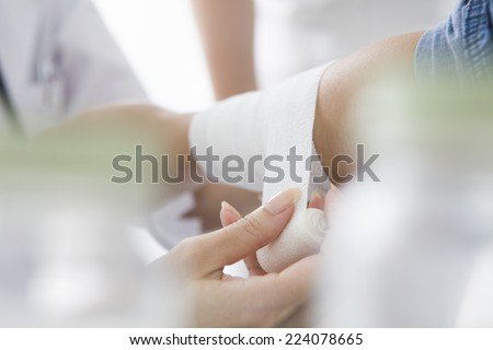 Nurse bandage to the patient's arm - stock photo