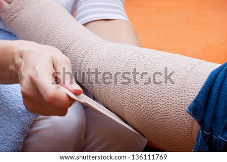 Nurse bandaged the foot of an adult senior - stock photo