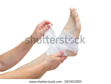 Nurse bandaging a broken ankle isolated - stock photo