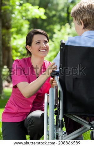 Nurse cares for an elderly woman in a wheelchair - stock photo