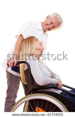Nurse caring for a young woman in wheelchair - stock photo