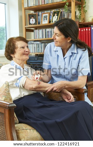 Nurse caring for senior at home smiling at eachother - stock photo
