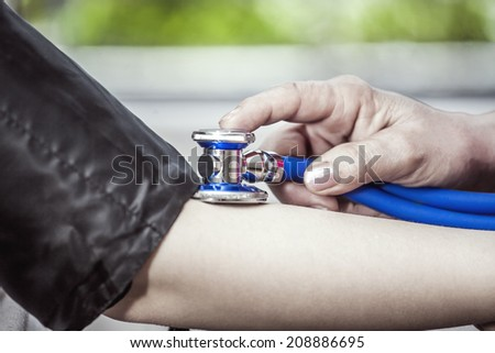 Nurse checking blood pressure with stethoscope - stock photo
