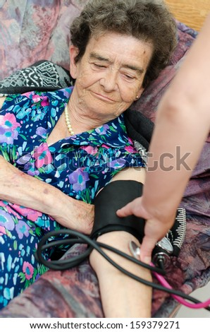 nurse checking senior woman blood pressure  - stock photo