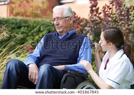 Nurse Comforting Senior Man In Wheelchair - stock photo