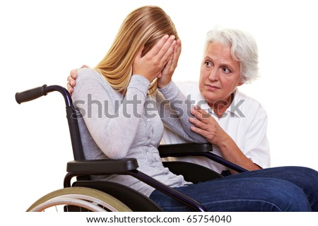 Nurse comforting young crying woman in wheelchair - stock photo