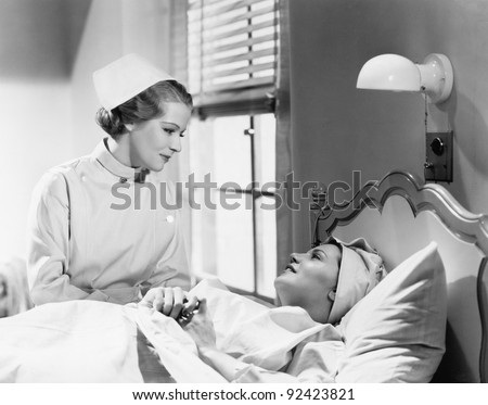 Nurse comforts a patient in a hospital bed, talking to each other - stock photo