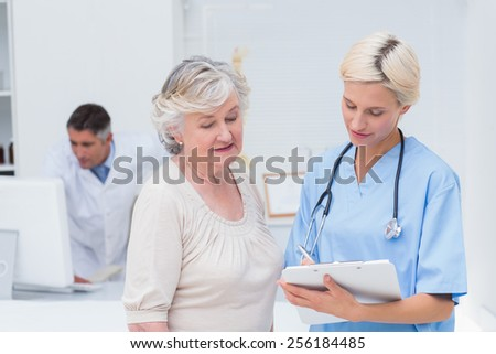 Nurse communicating with female patient while doctor using computer in background at clinic