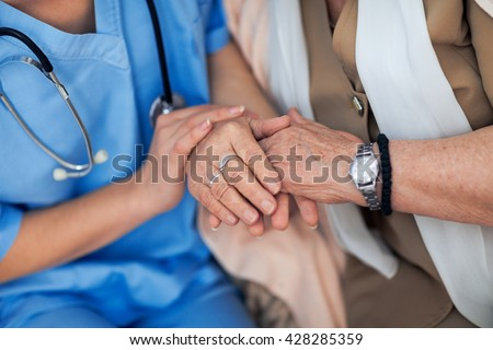 Nurse consoling and holding hands of an old woman - stock photo