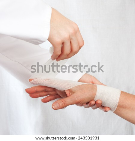 Nurse cover the hand of patient by bandage - stock photo