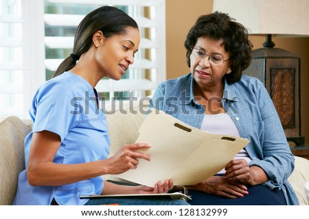 Nurse Discussing Records With Senior Female Patient During Home Visit - stock photo