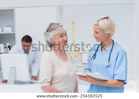 Nurse discussing with female patient while doctor using computer in background at clinic - stock photo