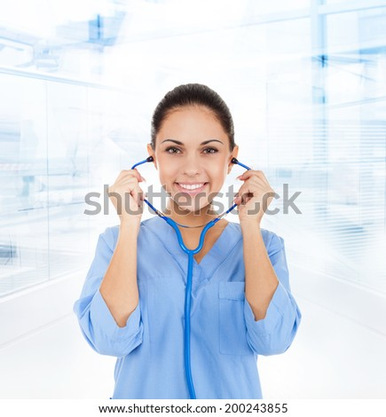 nurse doctor woman happy smile hold stethoscope, wear blue surgery medical suit in hospital - stock photo