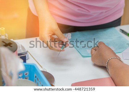 nurse drawing blood sample from arm patient for blood test - stock photo