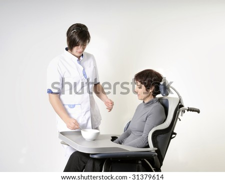 nurse feeding an adult disabled woman in wheelchair - stock photo