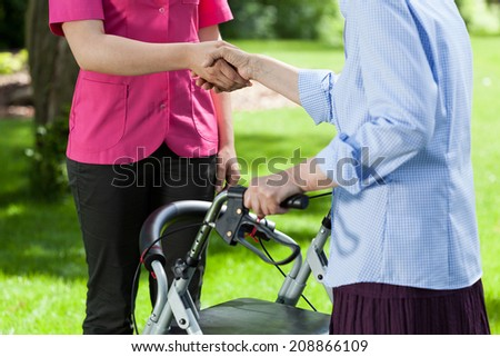 Nurse gives hand the older a woman in the park - stock photo