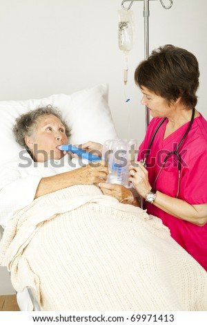 Nurse gives respiratory therapy to a patient recovering in the hospital. - stock photo