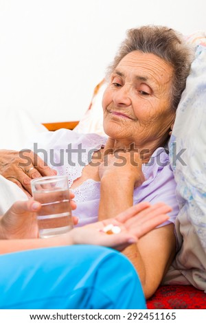 Nurse giving medication to elderly patient in nursing home. - stock photo