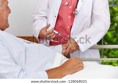 Nurse giving patient in hospital bed a syringe injection in the arm - stock photo