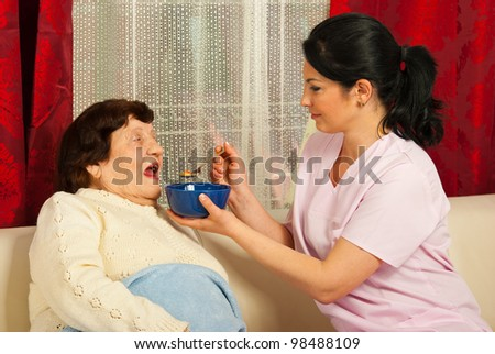 Nurse giving soup to sick elderly woman at home - stock photo