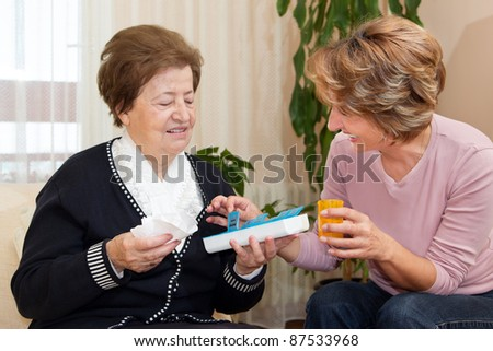 Nurse giving to senior woman the pill capsules from the box. - stock photo
