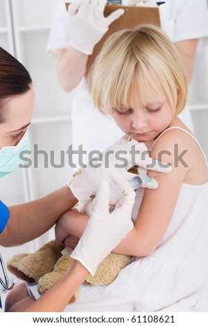 nurse giving vaccination injection to little girl patient