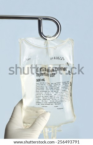 Nurse hangs sodium chloride IV solution on IV pole. - stock photo
