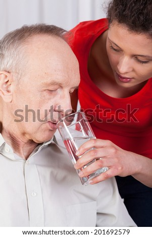 Nurse helping disabled man with drinking water - stock photo