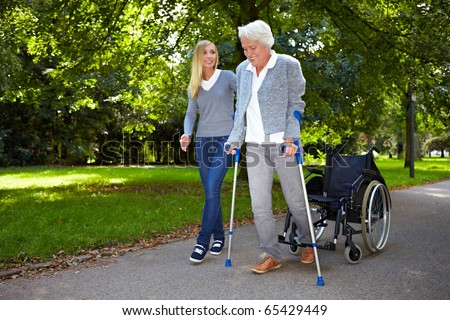 Nurse helping elderly woman with her physiotherapy outdoors - stock photo