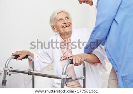 Nurse helping senior citizen patient in nursing home getting up - stock photo