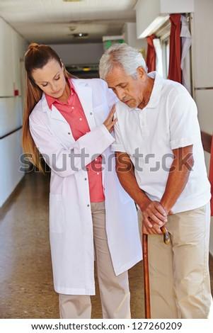 Nurse helping senior man with cane in a nursing home - stock photo