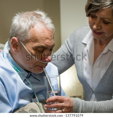Nurse helping senior sick man with drinking glass of water - stock photo