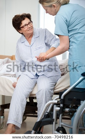 Nurse helps a patient to get up in hospital - stock photo
