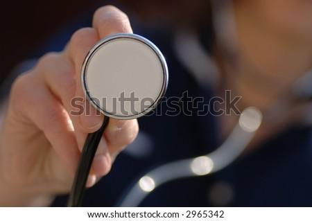 Nurse holding a stethoscope - stock photo