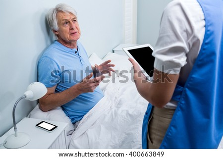 Nurse holding digital tablet while discussing with senior man at hospital - stock photo