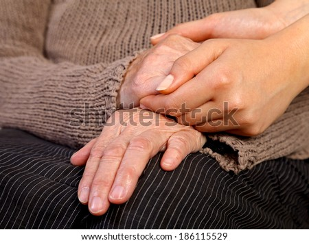 Nurse holding elderly wrinkled hand - stock photo