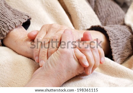 Nurse holding elderly wrinkled hands at home  - stock photo