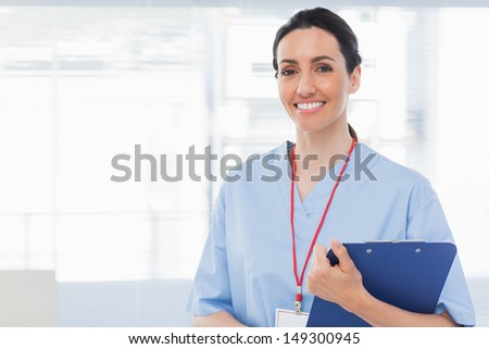 Nurse holding files in medical office - stock photo