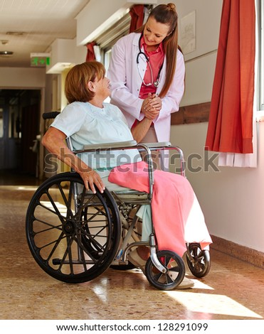Nurse holding hand of female senior patient in wheelchair - stock photo
