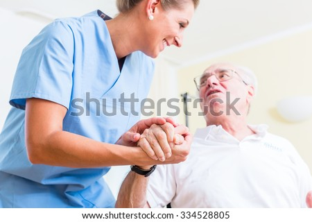 Nurse holding hand of senior man in rest home - stock photo