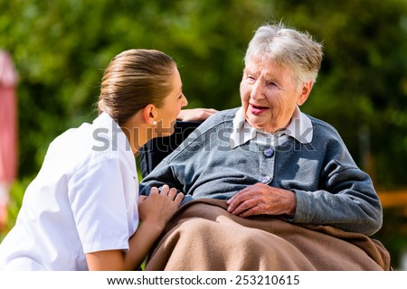 Nurse holding hands with senior woman sitting in wheelchair in garden of retirement home - stock photo