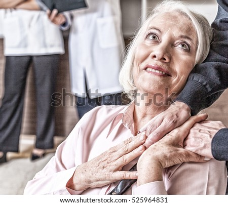 Nurse holding senior woman's hand in hospital. Healthcare concept.